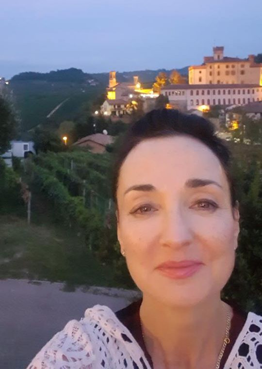 Kerin O'Keefe with Nebbiolo vineyards and Barolo Castle in the background